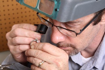 Jeweler Inspecting Benchmark Ring